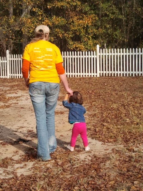 An adult and a toddler walking among fallen leaves on Thanksgiving