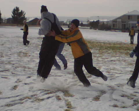 Friends playing football in the snow on Thanksgiving