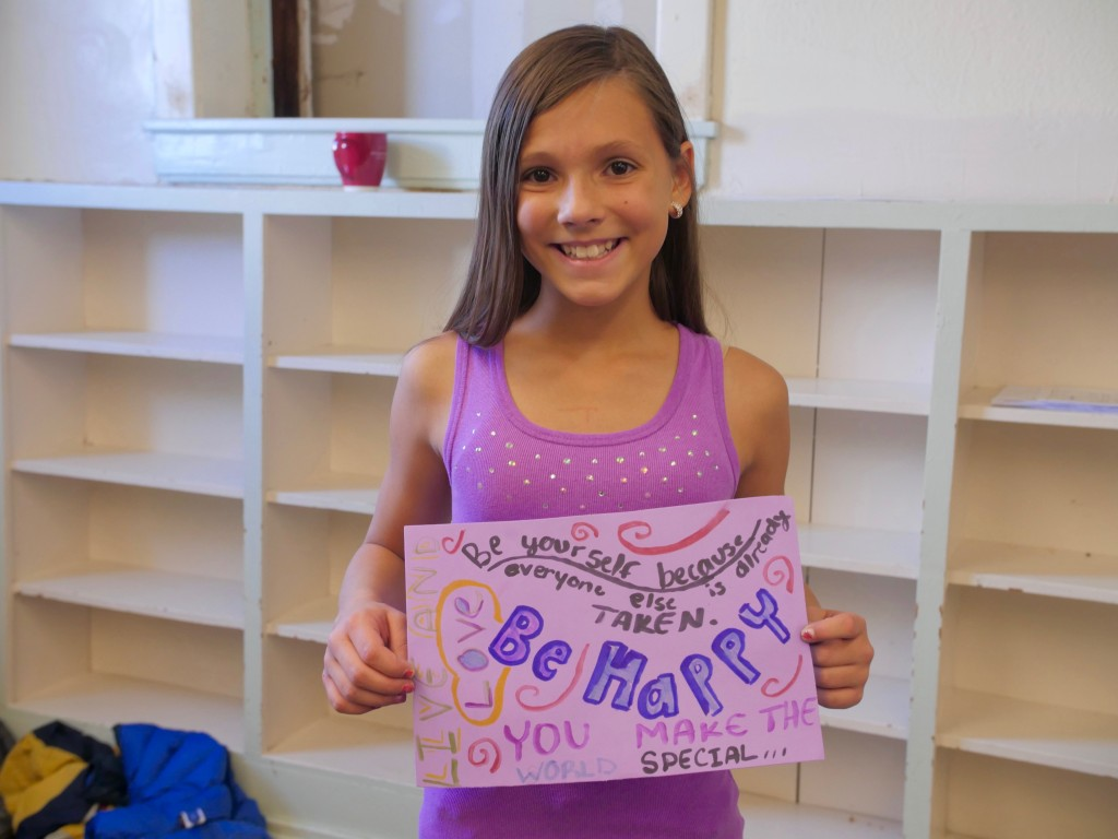 "Smiling girl with sign showing what ""Brave"" means to her. New Expression kids."