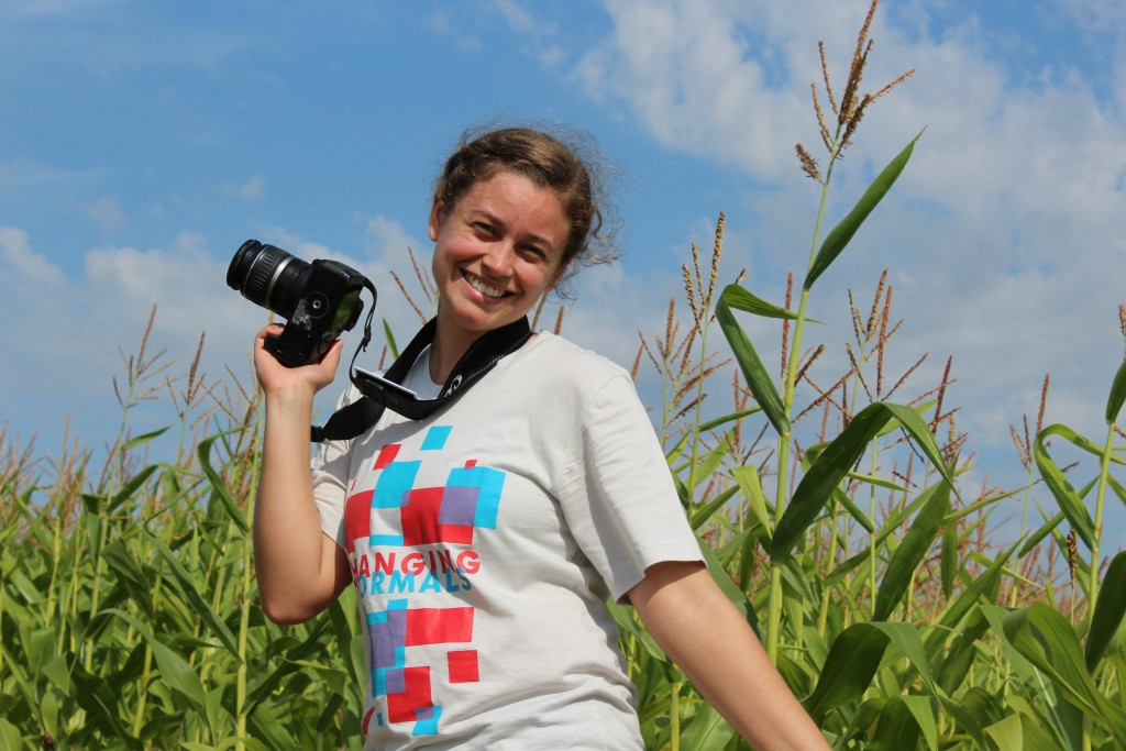 a photographer in front of a cornfield with camera in hand